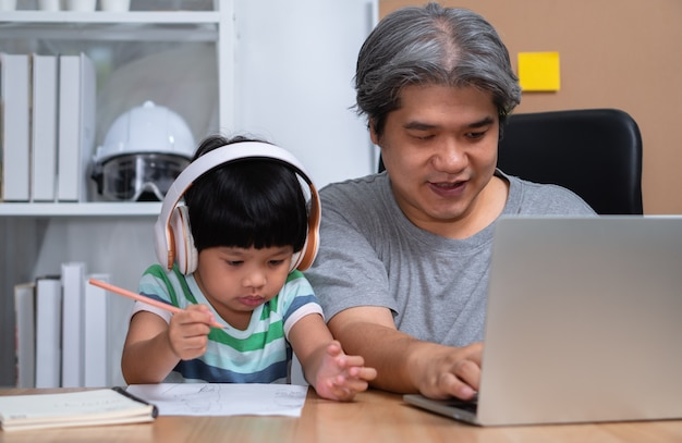 Asian father is work at the home with a daughter and studying online learning from school together