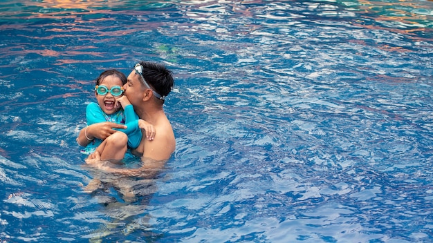 Asian father kissing and playing with his daughter in swimming pool