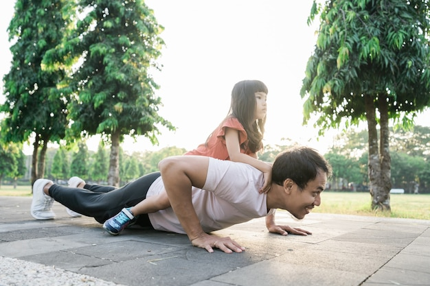 Asian father and little daughter do exercises in outdoor healthy lifestyle of family with child