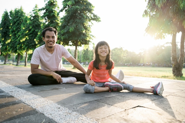 Asian father and little daughter do exercises in outdoor. healthy lifestyle of family with child
