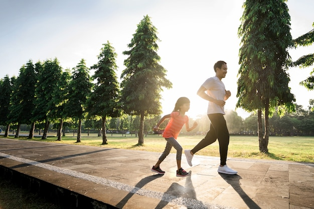 Asian father and little daughter do exercises running outdoor. healthy lifestyle of family with child