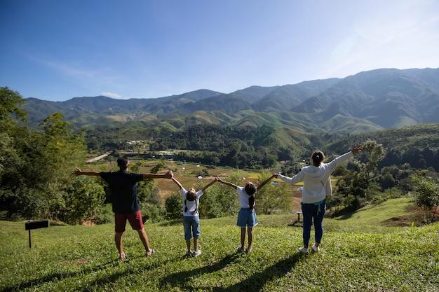 Азиатские отец, мать и дочери поднимают руки, глядя на красивую гору