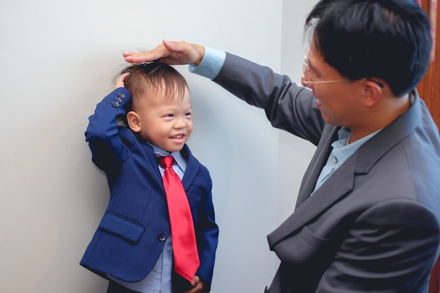 Asian father and son dressed in suits