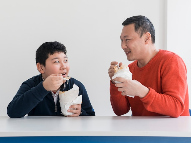 Asian father and son eating indoors