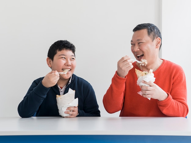 Asian father and son eating together