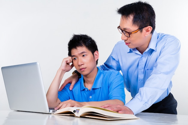 Asian father and son learning at home for school