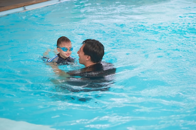 Asian father and son takes a swimming lesson at indoor swimming pool, cute little asian 3 years old toddler boy child wearing swimming goggles learning to swim with his dad