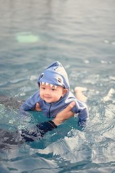 スイミングプールでかわいい愛らしい赤ちゃんと一緒に泳ぐアジアの父