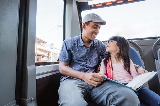 バスの公共交通機関に乗って勉強して娘を学校に連れて行くアジア人の父親