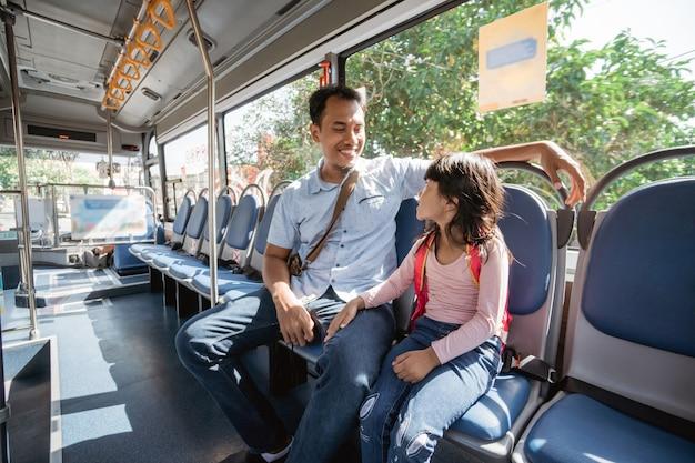 バスの公共交通機関に乗って娘を学校に連れて行くアジア人の父親