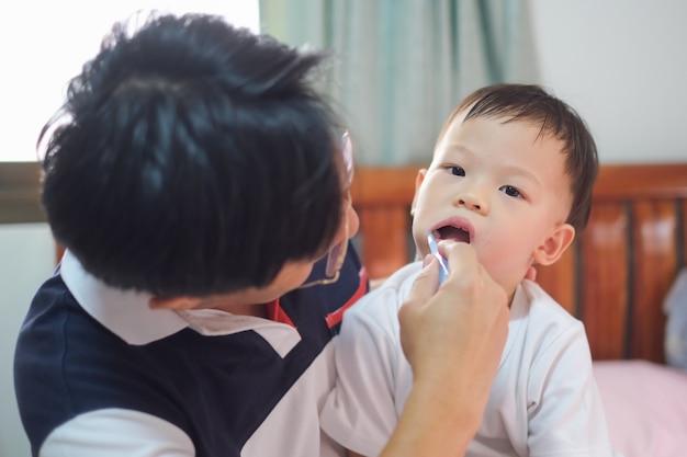 アジアの父が子供の歯のブラッシングを教える、かわいい2-3歳の幼児男の子子供が自宅のベッドで朝の歯を磨くことを学ぶ、子供の歯のケア、子供の開発コンセプト