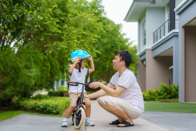 Asian father wears a helmet for his son while teaching his child how to ride a bicycle in a neighborhood garden, fathers interact with their children throughout the day.