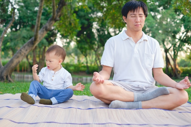 Asian father with eyes closed and 1 year old toddler boy child practices yoga & meditating outdoors on nature in summer, healthy lifestyle concept
