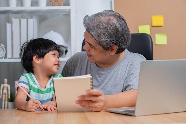 Азиатский отец работая на домашнем офисе с компьтер-книжкой и уча домашнюю работу с дочерью.