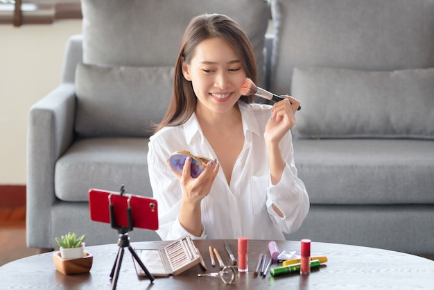 Asian female beauty influencer making a video tutorial for her beauty channel on cosmetics during stay safe at home