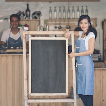 Asian female cafe owner with blank board