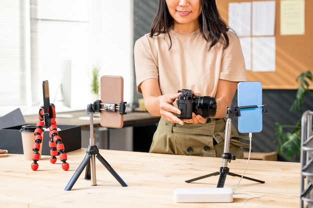 Asian female in casualwear holding photocamera on wooden table while unpacking it and recording the process on smartphone camera