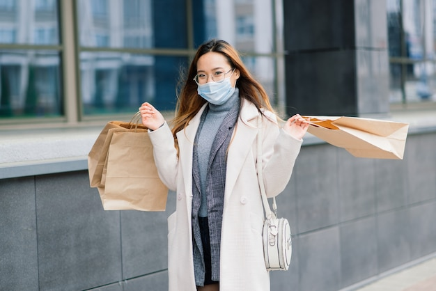 Asian female in a coat, glasses and a medical mask stands on the street, holding a package in her hands.