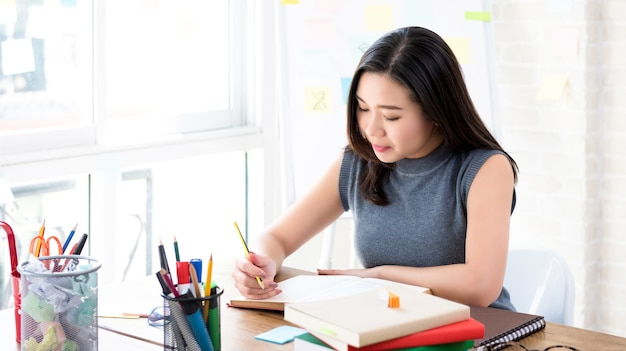 Asian female college student reading book at the table