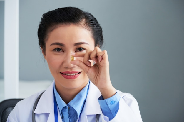 Asian female doctor holding pill in front of her face