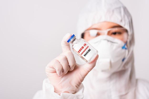 Ppeの制服を着たアジアの女性医師と薬瓶コロナウイルスワクチンボトルを保持している研究室で保護フェイスマスクを着て手袋