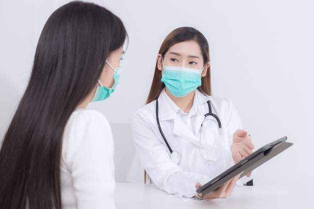 An asian female doctor is talking to a female patient about his pain and symptoms in the hospital.