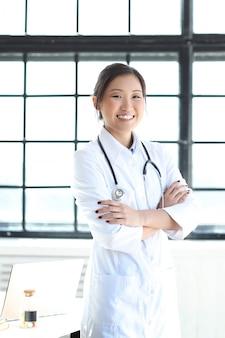 Азиатский женский доктор представляя усмехаться