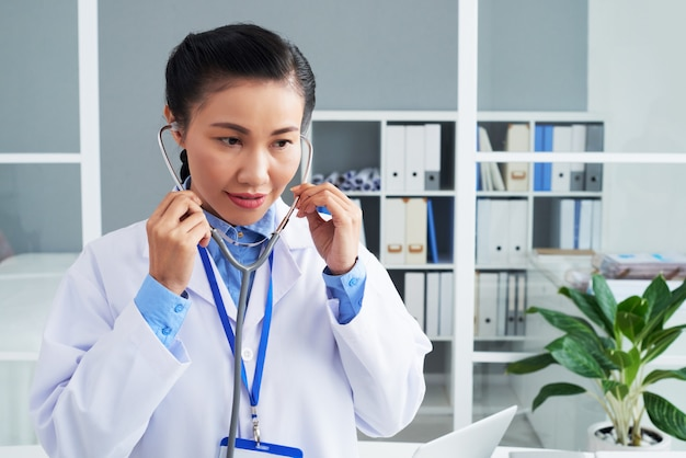 Asian female doctor putting on stethoscope at work