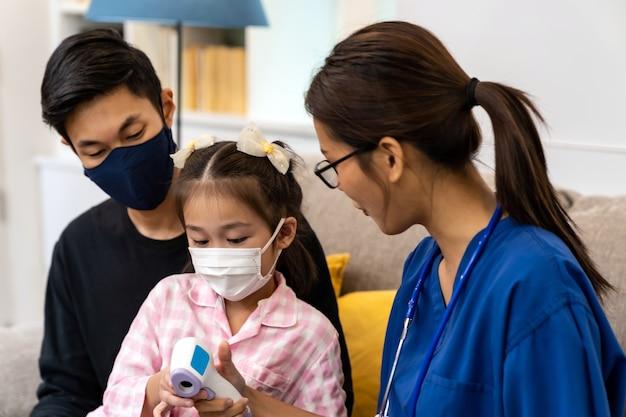 アジアの女性医師は、医師が自宅を訪問している間、小さな女の子の子供がお父さんとリビングルームに座っているときに赤外線温度計を使用して温度を示します。在宅医療の提供と医師の訪問の概念。