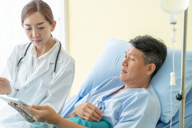 Asian female doctor sitting on hospital bed and discussing with senior patient