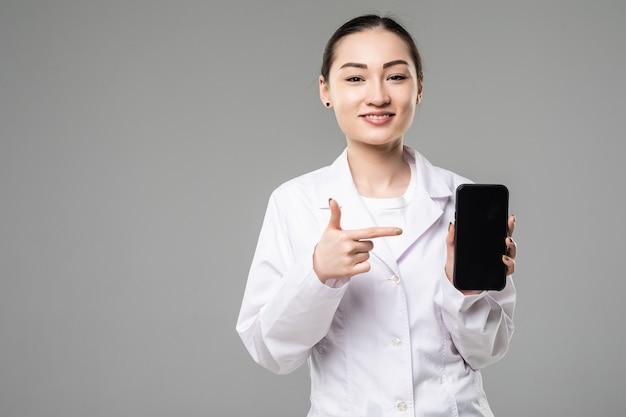 아시아 여성 의사가 웃고 흰 벽에 격리된 빈 스마트 폰 화면을 보여줍니다.