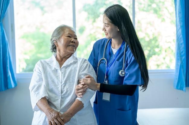 アジアの女性医師が世話をし、病院で高齢患者と話し合い、ヘルスケアと共感の概念。