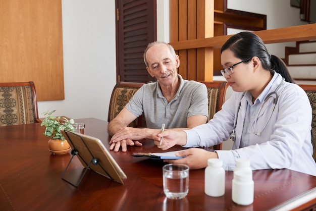 Asian female doctor talking to senior caucasian patient during house call