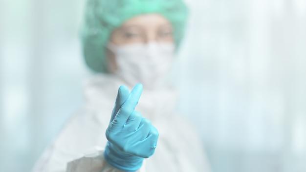 Костюм hazmat азиатского женского доктора нося делает миниую руку знака сердца.