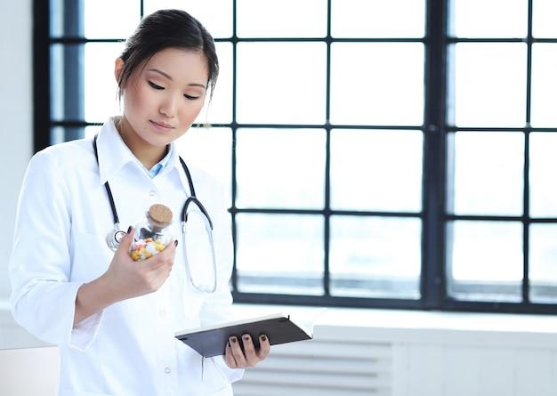 Азиатский женский доктор, специалист по женщины с тетрадью и пилюльки