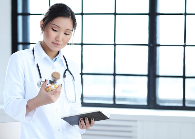Asian female doctor, woman specialist with notebook and pills