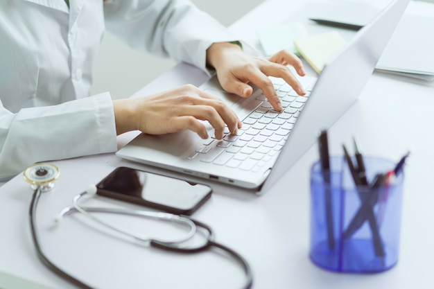 オフィスでコンピューターを使用して作業しているアジアの女性医師