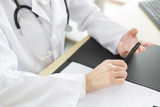 아시아 여성 의사들이 병원에서 환자들의 질병 치료에 대해 설명하고 있다.