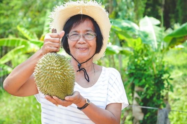 Asian female elderly farmers wearing hats, holding 1 durian fruits