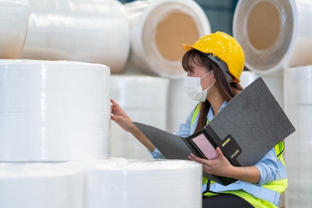 아시아 여성 엔지니어는 창고 공장 산업에서 제품 재고를 확인하는 문서를 보유하고 있습니다.