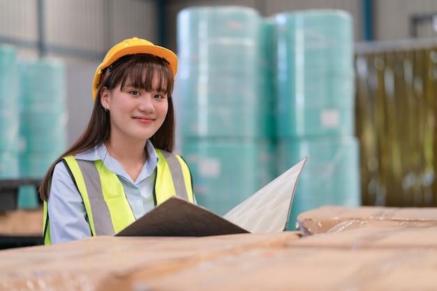 아시아 여성 엔지니어는 창고 공장에서 제품 재고를 확인하는 문서 폴더를 보유하고 있습니다.