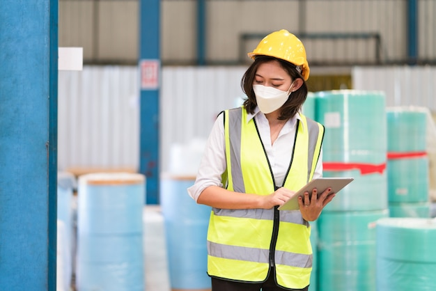 Asian female engineer wear mask protect holding tablet checking stock product in warehouse factory