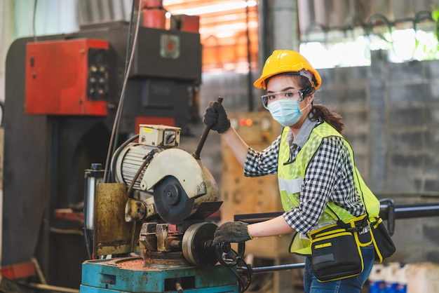 Asian female engineers wearing hygienic mask protect with helmet safety in factory industrial