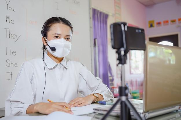 マスクをかぶったアジアの女性英語教師が、教育用のオンラインビデオ会議システムを使用してコンピューター画面でオンラインで勉強することを生徒に教えています。