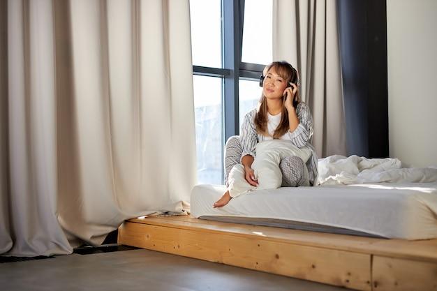 アジアの女性はベッドに座ってヘッドフォンで音楽を楽しんでいます、パジャマの幸せな女性は寝室に一人で座っています