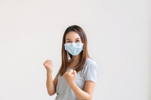 Asian female in face mask on white background raising hands in fists and screaming with happiness.