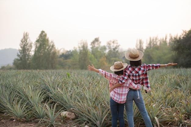 아시아 여성 농부는 농장, 농업 산업 개념에서 파인애플의 성장을 참조하십시오.