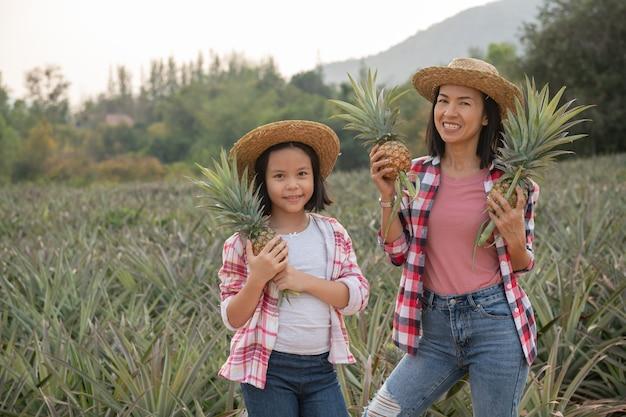 アジアの女性農民は、農場でパイナップルの成長を見ています、農業産業の概念。