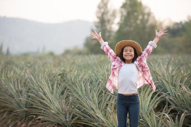 アジアの女性農民は農場でパイナップルの成長を見ます、腕を持って農地に立っている若いかわいい農夫の女の子は喜びに満ちた高揚した幸福を上げました。