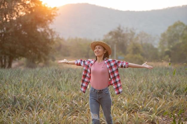 Азиатская женщина-фермер видит рост ананаса на ферме, молодая красивая женщина-фермер, стоящая на сельскохозяйственных угодьях с поднятыми руками, радостное, приподнятое счастье.